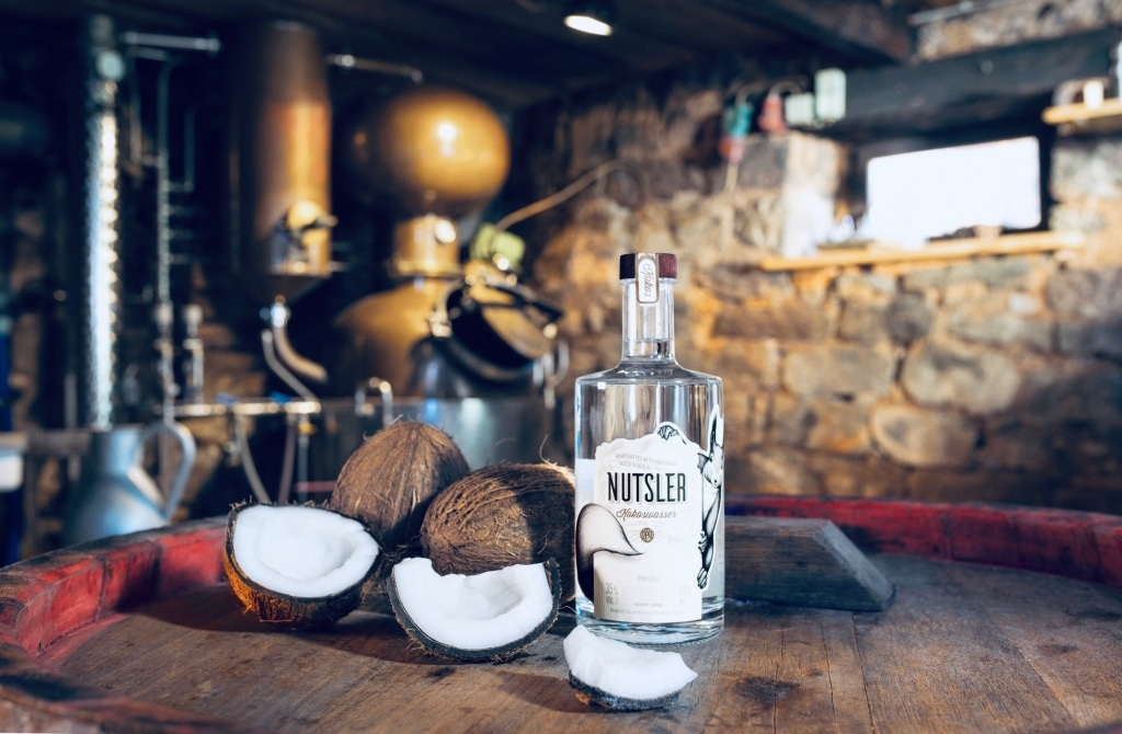 Kokos Nutsler in der Flasche mit aufgeschlagener Kokosnuss