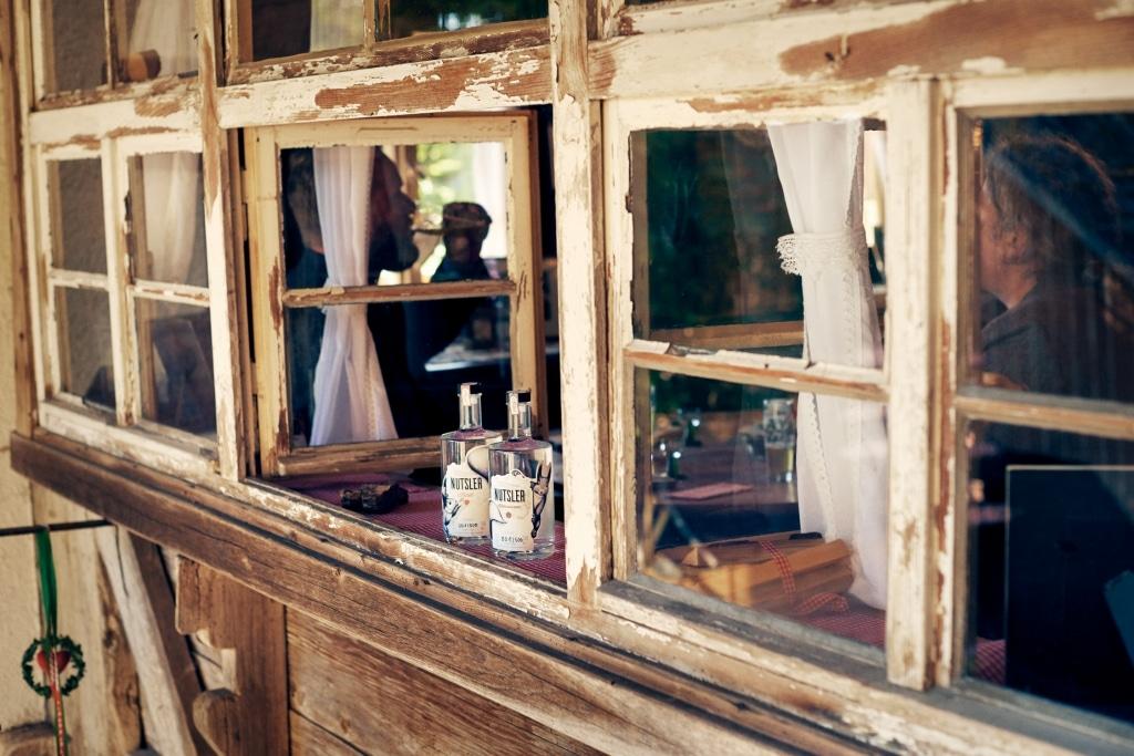 Zwei Flaschen Nutsler Spirituosen auf dem Fensterbrett von altem Fachwerkhaus