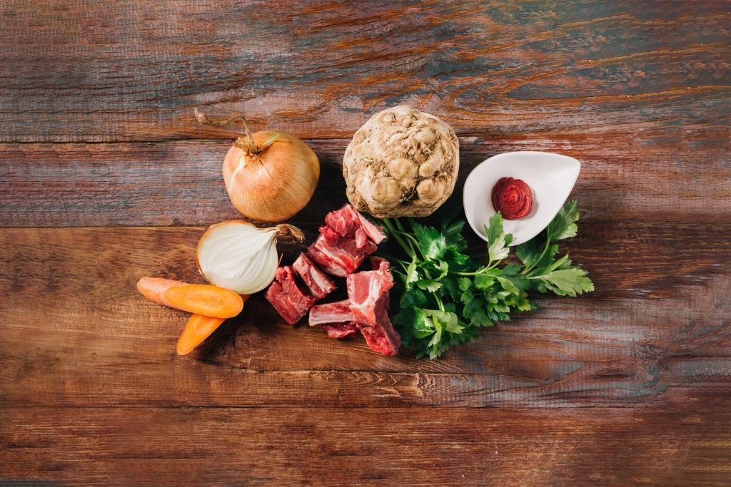 Gemüse, Fleisch und frische Petersilie auf Holzbrett von Benz Feinkostmanufaktur