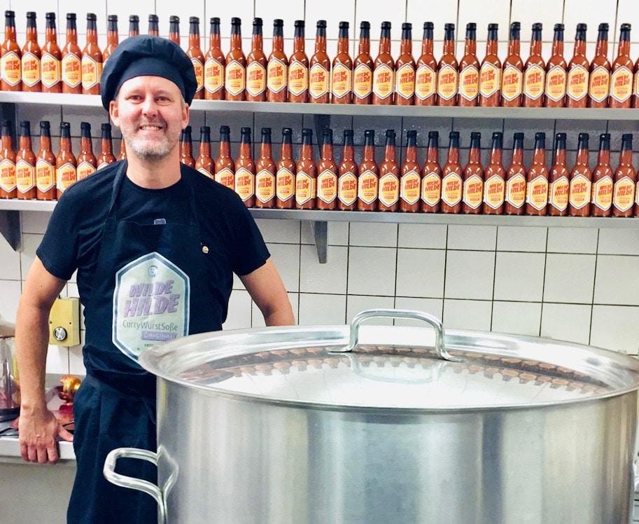Christian Hübner von der Wilden Hilde mit riesigem Kochtopf in der Küche