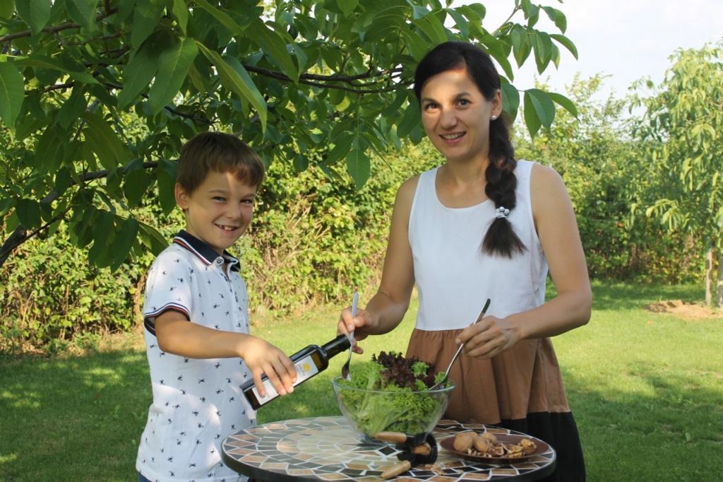 Frau und Kind würzen Salat mit Walnussöl von der Manufaktur Gelbe Bürg