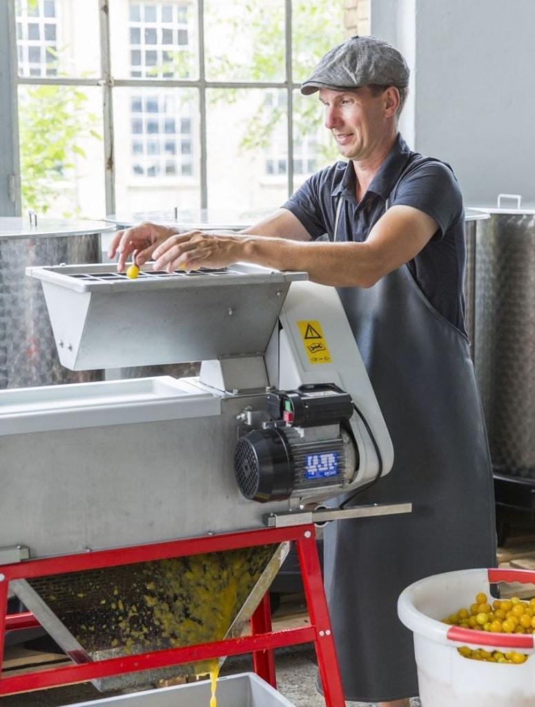 Matthias Rosenberg presst seine Pflaumen für Rosenberg Delikatessen in einer Maschine