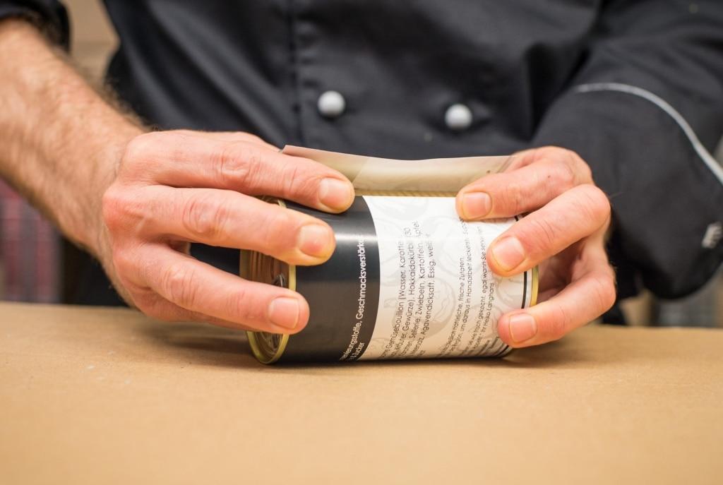 Heiko von der Langhans Suppenmanufaktur etikettiert eine Dose von Hand
