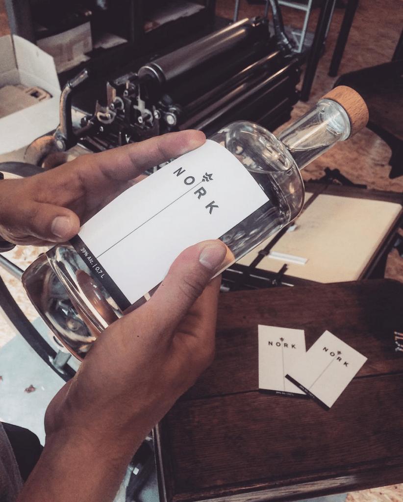 Kornflasche von NORK wird von Hand etikettiert