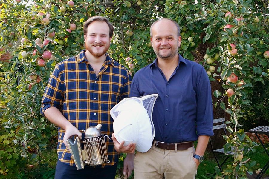 Ingo und Benedikt von herr Biene mit Imkerhut vor Apfelbäumen